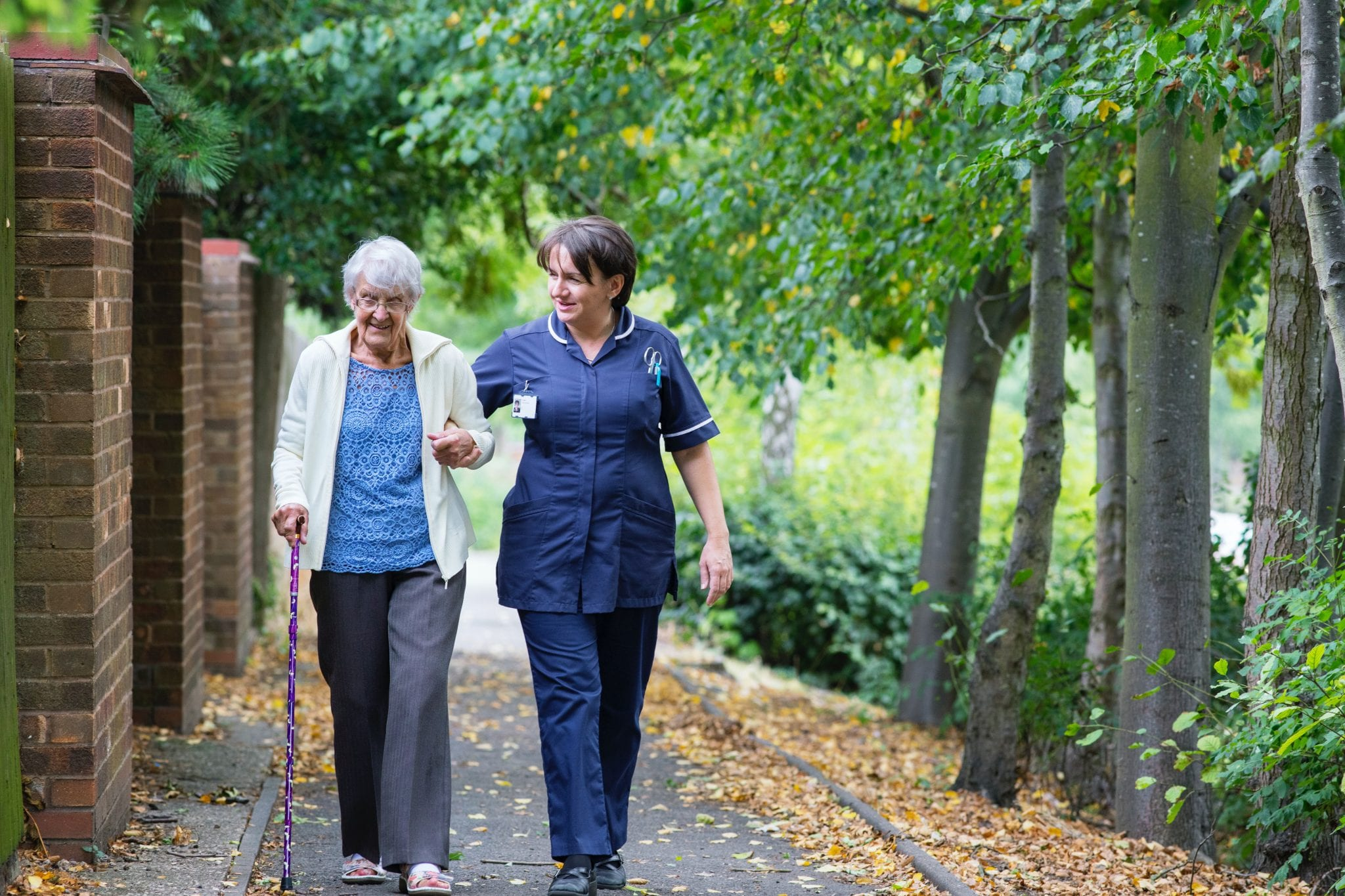 man in blue polo shirt and woman in white dress walking on pathway