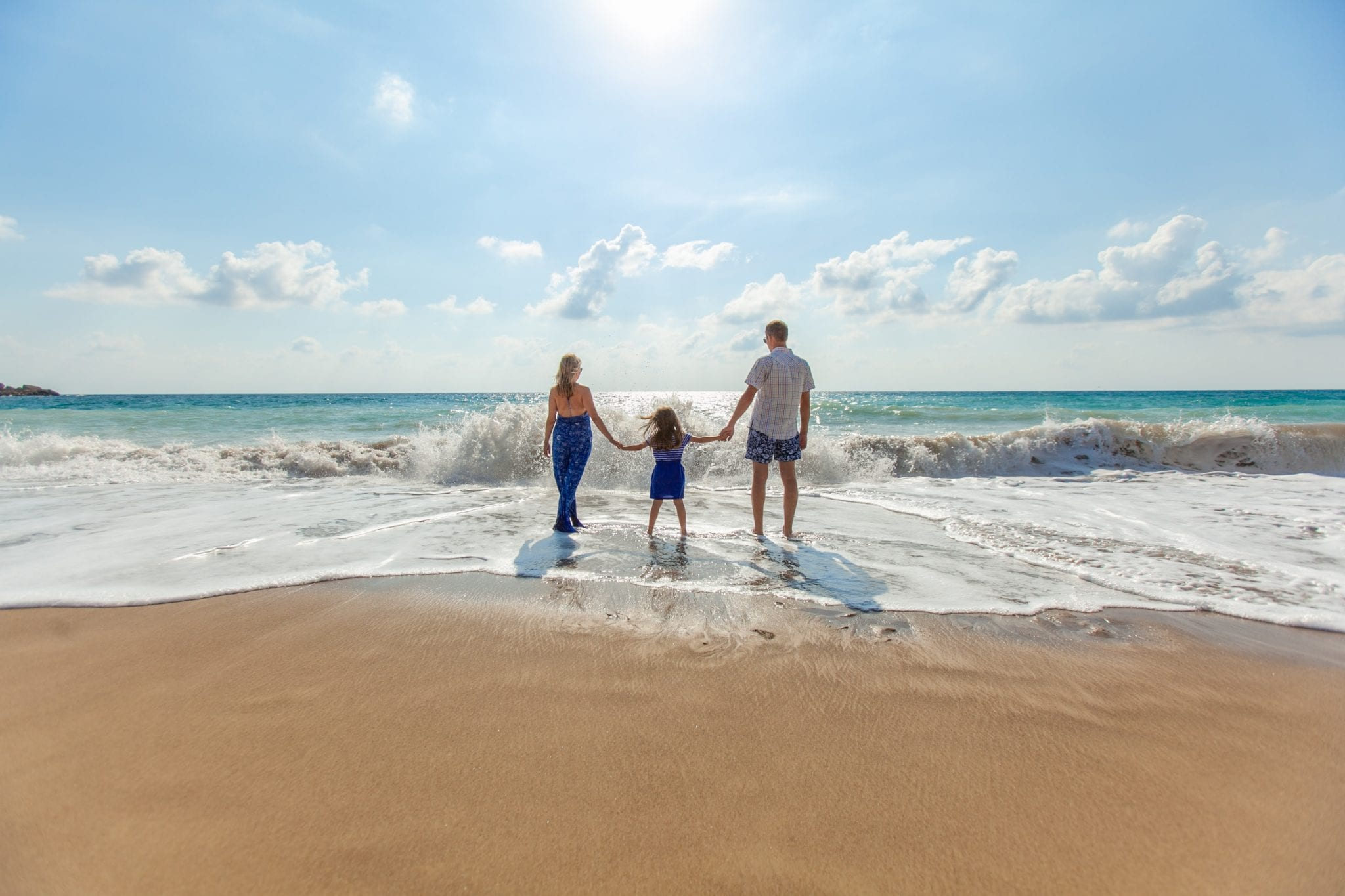 man, woman and child holding hands on seashore
